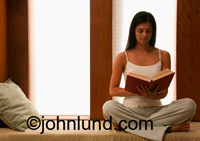 Photo of a beautiful Latina woman sitting on her bed and reading a book. She has a perfect posture, long brown hair and is wearing a white tank top. She is barefoot.
